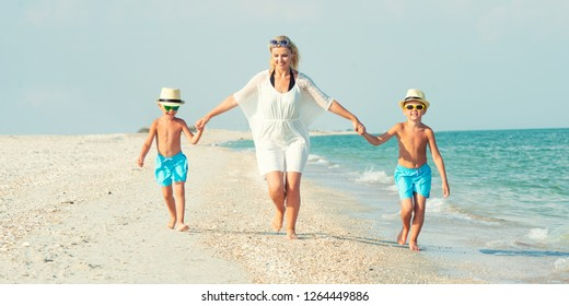 Family walking on the beach Mother and two sons.