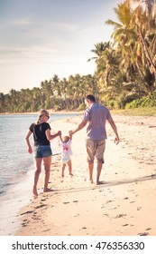 Family walking on beach. Mother and father holding child in hands while walking on tropical beach during sunset