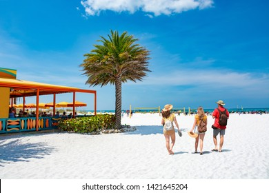 Family walking on beautiful white sand beach on summer vacation in Florida Volleyball nets, beach umbrellas and green ocean in background.  Gulf of Mexico, Clearwater Beach, Florida, USA.