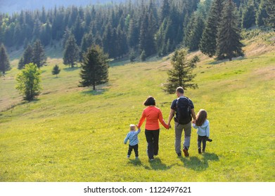 family walking on meadow at pine forest