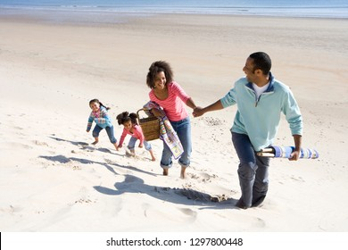 Family walking on sand dune by beach with picnic basket and windbreak