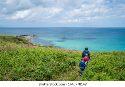 Family walking on a small path along the stunning Cornish coastline near St. Ives in Cornwall, England, UK