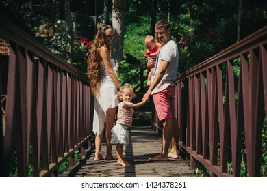 Family walking on wooden bridge in Bali. Mother, father and children have a vacation in tropic Asia
