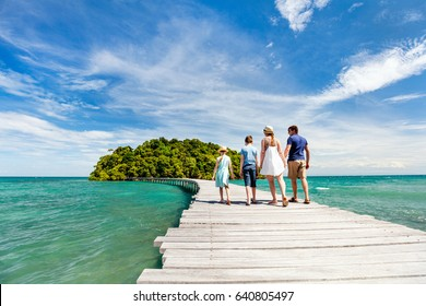 Family walking on wooden pathway leading to beautiful tropical island in Cambodia