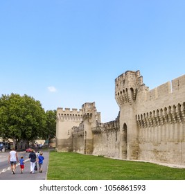 Family walking outside the historic fortified walls of Avignon in France