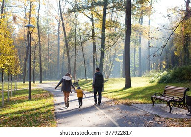 a family walking in the park in autumn