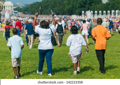 A family walking with purpose and pride at a rally on the National Mall in Washington, DC.