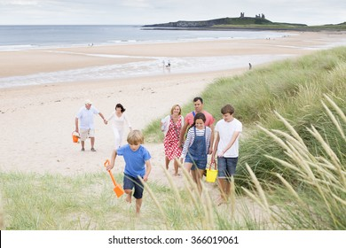 A family are walking up the sand dunes, leaving the beach. They are all smiling and talking with each other.