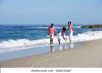 Family walking in surf on sandy beach summer vacation holding hands side by side with waves breaking on shore