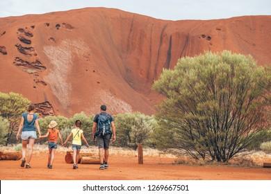 A family walking through the Australian bush of the outback desert, the red centre of Australia