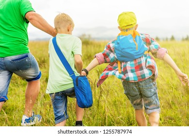 Family is walking together around the park and meadow, having fun