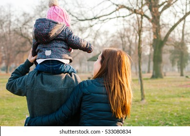Family walking together in a park. A father holding his daughter on his shoulders