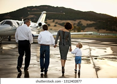 Family walking towards a private jet holding hands