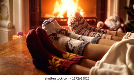 Family in warm woolen socks lying on sofa next to burning fireplace