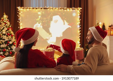 Family watching movie on projection screen in room decorated for Christmas, back view. Home TV equipment