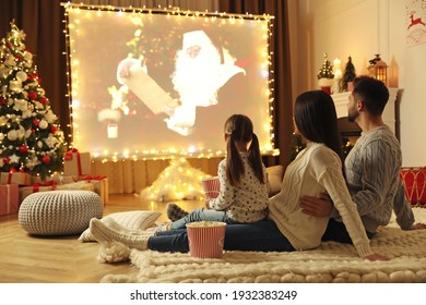 Family watching movie on projection screen in room decorated for Christmas. Home TV equipment