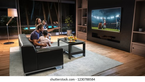 A family is watching a soccer moment on the TV and celebrating a goal, sitting on the couch in the living room. The living room is made in 3D.