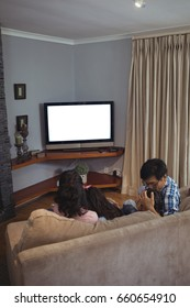 Family watching television together in living room at home
