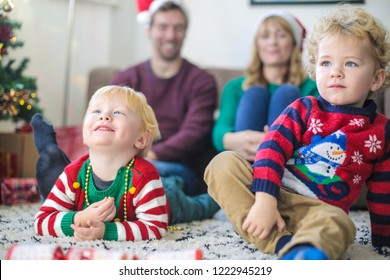 Family watching tv all together, wearing christmas clothes