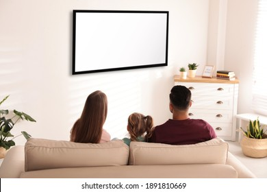 Family watching TV on sofa at home, back view