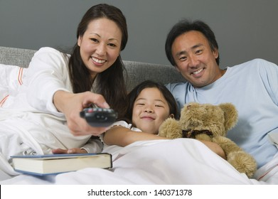 Family watching TV together in bed while mother using remote control at home