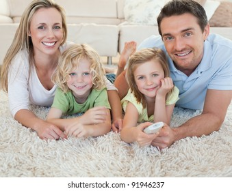 Family watching tv together on the floor
