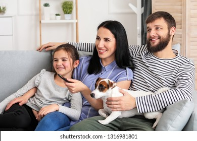 Family watching TV while sitting on sofa at home