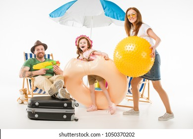 Family with water gun, flotation ring and ball isolated on white, travel concept