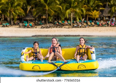 Family at water tube crazy sofa on the beach smiling