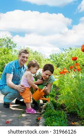 Family watering flowers in their garden
