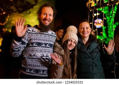 Family waving for photo in traditional Christmas market, Zagreb, Croatia.