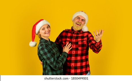 Family wear santa hats. Entertainment ideas for adults. Santa team. Loving couple yellow background. Christmas magical time. We love christmas. Couple in love enjoy christmas holiday celebration.