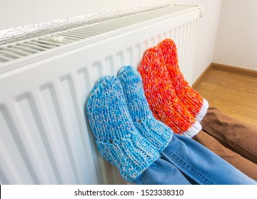 Family wearing colorful pair of knitted wool socks warming cold feet in front of heating radiator in winter time. Electric or gas heater at home. The symbolic image of the heating season at home.