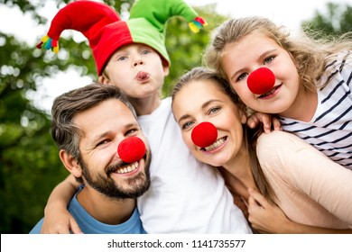 Family wearing costumes and red nose having fun at carnival