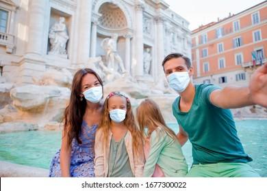 Family wearing face masks at Fontana di Trevi, Rome, Italy. Coronavirus flu virus travel concept banner.