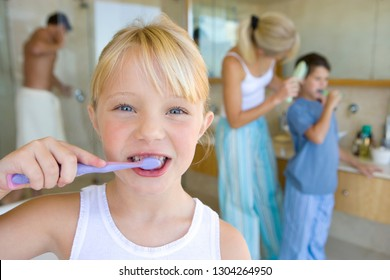 Family wearing pajamas brushing teeth in bathroom in morning