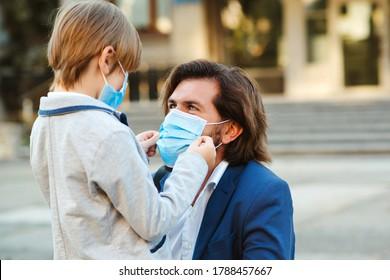 Familie, die während der Quarantäne Schutzmasken trägt. Ausbruch von Coronavirus. Papa zieht eine Schutzmaske auf das Gesicht seines Sohnes an. Medizinische Maske zur Vorbeugung gegen Coronavirus. Coronavirus-Pandemie