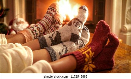 Family wearing woolen socks warming feet at fireplace on Christmas eve