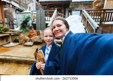 Family wearing yukata Japanese kimono making selfie at street of onsen resort town in Japan. Translation of text on wooden plate: passport for round bath visit to protect you from bad luck.
