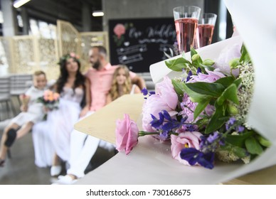 family at the wedding, ceremony, groom, bride and children. in room. flowers and decor in the foreground