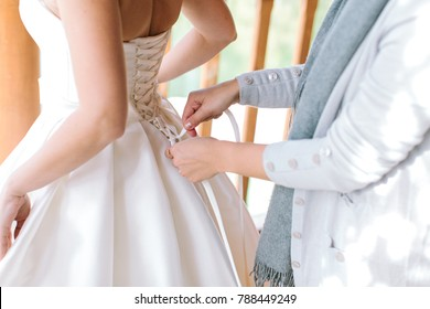 family, wedding day, relationships concept. caring mother is helping her graceful daughter for important preparation and dressing her radiant white dress of bride
