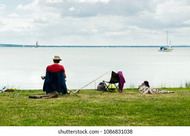 The family weekend and the active leisure time during summer vacation on the famous spa resort Lake Balaton in Hungary - a man fishing with rod while a kid is sleeping on the green grass lawn