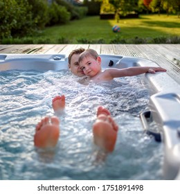 Family weekend in summer cottage, local staycation. Cute kid with father having rest together in bathtub with bubby water one hot day, happy summertime, outdoor lifestyle