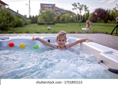 Family weekend in summer cottage, local staycation. Cute kid having rest in bathtub with bubby water one hot day, happy summertime, outdoor lifestyle