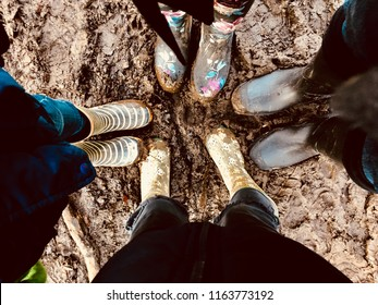 Family with wellies in mud on woodland walk