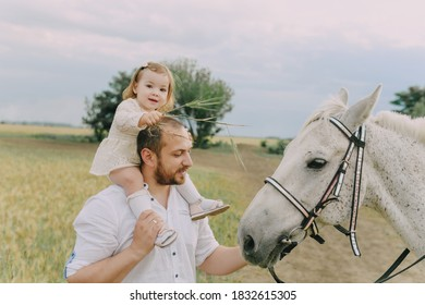 Family in white clothes in a field with a horse