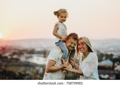 Family in white shirts covered with different paints stands outside in the evening