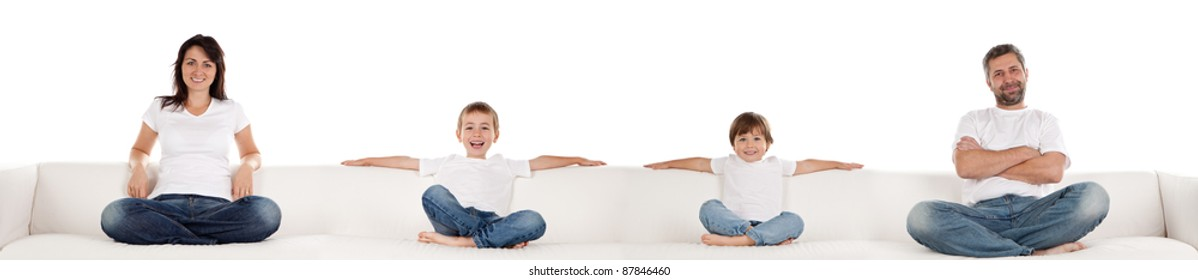 Family in white tshirts and denim jeans sitting on long white couch. Panorama format, isolated.