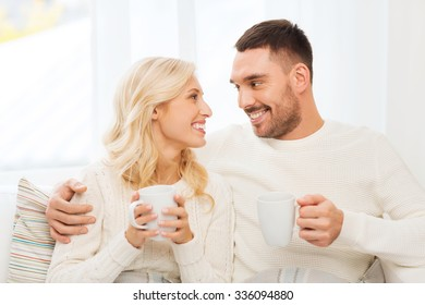 family, winter, holidays, love and people concept - happy couple covered by plaid with cups drinking tea and sitting on sofa at home