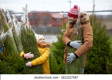family, winter holidays and people concept - happy father and little daughter buying christmas tree at street market - Shutterstock ID 1812227587